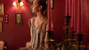 Professional fashion model with a tail poses for a photographer indoors in vintage style. fashion industry, beauty, backstage stock footage