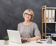 Professional female administrative manager working on laptop in office. Professional female administrative manager in glasses working on laptop in office Stock Photography