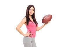 Professional female athlete holding a football Stock Photos