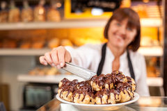 Professional female baker is selling baked. Cheerful saleswoman is standing at the counter in bakehouse. She is taking sweet cookie from the plate. The woman is Royalty Free Stock Images