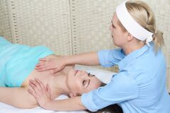Professional female cosmetologist doing facial massage to woman in spa salon