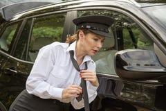 Professional female car driver adjusting her tie Stock Image