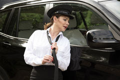Professional female car driver adjusting her tie Stock Images