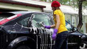 Professional female car washer cleaning car window with soapy sponge. stock footage
