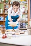 Professional Female Ceramist in Apron Glazing Ceramic Bowl. On Turntable in Workshop. Vertical Image Orientation Stock Photo