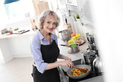 Professional female chef cooking vegetables royalty free stock photo