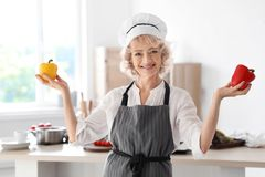 Professional female chef holding pepper near table royalty free stock images