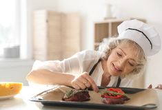 Professional female chef preparing meat on table royalty free stock photos
