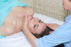 Professional female beautician doing facial massage to woman in spa salon