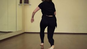 Professional female dancer exercising in a dance hall. Slow motion stock footage
