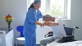 Professional female doctor helping her patient to sit in the wheelchair. Have a sit. Professional helping doctor helping her senior immobile patient to sit in stock video