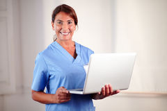 Professional female doctor holding a laptop Stock Photo