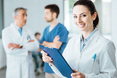 Professional female doctor posing and smiling Royalty Free Stock Photos