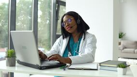 Professional african american female doctor in white medical coat and headset making conference call on laptop computer