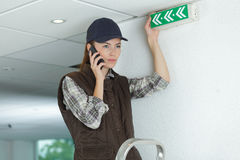Professional female electrician on phone. Professional female electrician on the phone Royalty Free Stock Images