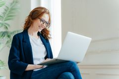 Professional female employer enjoys working process, sits crossed legs with laptop device, chats online, has positive look, has royalty free stock photo