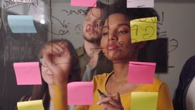 Professional female executive standing with her colleague writing down business ideas on sticky notes and glass board at. Businesswoman making a business plan on stock video