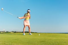 Professional female golf player smiling while swinging a driver club. Full length of a professional female golf player smiling while swinging a driver club with Royalty Free Stock Photos