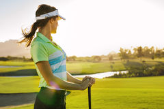 Professional female golfer looking away. Professional female golfer holding golf club on field and looking away. Young woman standing on golf course on a sunny Royalty Free Stock Photography