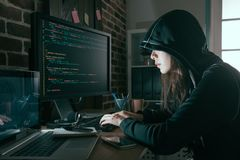 Professional female hacker using keyboard typing. Young professional female hacker using keyboard typing bad data into computer online system and spreading to stock images