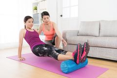 Professional female individual home fitness tutor. Pretty professional female individual home fitness tutor teaching student using yoga roller workout body royalty free stock photography