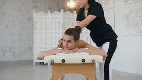 Professional female masseur making relaxing massage in spa salon.