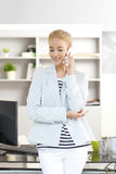 Professional female with mobile phone. Portrait of young assistant standing at office in front of her computer while looking at camera and making call Royalty Free Stock Photos