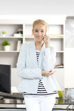 Professional female with mobile phone. Portrait of young assistant standing at office in front of her computer while looking at camera and making call Royalty Free Stock Image
