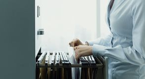 Office clerk searching files in the filing cabinet stock image