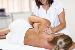 Professional female physiotherapist giving shoulder massage to b. Londe women in hospital. Medical check at the shoulder in a physiotherapy center Stock Photos