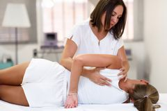 Professional female physiotherapist giving shoulder massage to b. Londe women in hospital. Medical check at the shoulder in a physiotherapy center royalty free stock photo