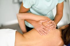 Professional female physiotherapist giving shoulder massage to a. Professional female physiotherapist giving shoulder massage to brunette women in hospital stock images