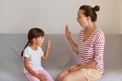 Professional female physiotherapist working on speech defects or difficulties with small child girl indoors while sitting on sofa