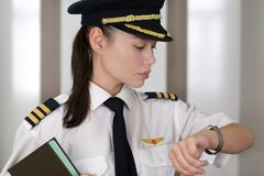 Professional female pilot checking the time at he airport stock image