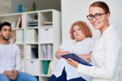 Professional Female Psychiatrist Leading Group Therapy Session. Portrait of beautiful female psychologist smiling to camera holding clipboard while leading group Stock Photo