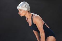 Professional female swimmer on black background Stock Images