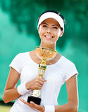 Professional female tennis player. Young female tennis player won the cup at the sport competition. Prize Royalty Free Stock Photo
