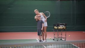 Professional female tennis player standing behind her little apprentice holding his hand and showing correct impact stock footage