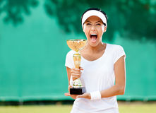 Professional female tennis player won the cup. Tennis player won the cup at the sport competition. Award Royalty Free Stock Image