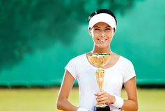 Professional female tennis player won the match. Tennis player won the cup at the sport contest. Prize Royalty Free Stock Image