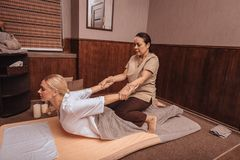 Professional female Thai masseuse doing the massage. Professional massage. Professional Thai masseuse holding her clients hands while doing the massage royalty free stock image