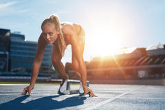 Professional female track athlete on sprinting blocks. Professional female track athlete in set position on sprinting blocks of an athletics running track Stock Photography