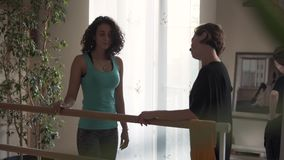 Professional female trainer consulting her client about exercises that she has to do. Fitness trainer working with the. Young girl at home or in the modern stock footage