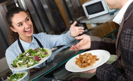 Professional female worker serving customer with smile. At shawarma place Stock Image