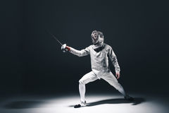 Professional fencer in fencing mask with rapier standing in position. On grey stock images