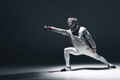 Professional fencer in fencing mask with rapier standing in position. On grey royalty free stock images