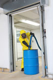 Professional filling large barrel with chemicals. Fully protected in yellow uniform,mask,and gloves professional filling large blue barrel with chemicals royalty free stock images