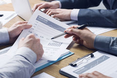 Professional financial service. Business professionals working together at office desk, hands close up pointing out financial data on a report royalty free stock photos