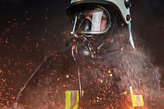 A firefighter dressed in a uniform in a studio. stock photography