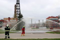 Professional firefighters in orange fire-resistant suits in white helmets with gas masks are testing fire hoses and fire guns to e royalty free stock photography